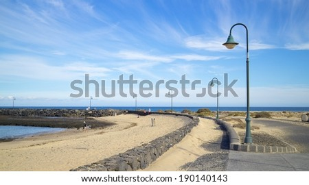 Las Cucharas beach walk with typical street lamps on Lanzarote island, Spain - stock photo