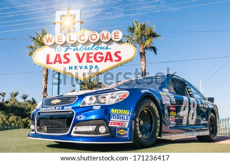 "LAS VEGAS - DECEMBER 6, 2013: Chevrolet SS vehicle number 48 of the NASCAR world champion driver Jimmie Kenneth Johnson, in front of the famous ""Welcome Sign"" at the beginning of Las Vegas Boulevard. - stock photo"