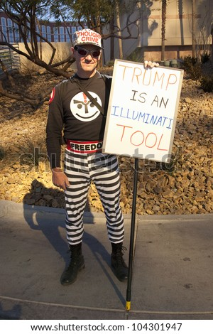 "LAS VEGAS - FEB 2: A protestor holds a sign which reads ""Trump is an Illuminati Tool"" outside the Trump hotel on February 2, 2012 in Las Vegas, Nevada. Trump is endorsing Romney for president. - stock photo"