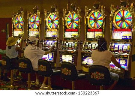 LAS VEGAS, NEVADA - CIRCA 2004: Gamblers putting coins into slot machines in Las Vegas, NV - stock photo