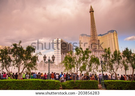 LAS VEGAS, NEVADA - MAY 7, 2014:  Visitors viewing the famous Fountains at the Bellagio Hotel and Casino at sunset with Paris Vegas in the background. - stock photo