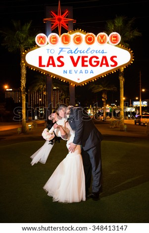 LAS VEGAS, NV - DECEMBER 12, 2014: Bride and groom kissing in front of the historic Welcome to Fabulous Las Vegas Nevada sign at night. - stock photo