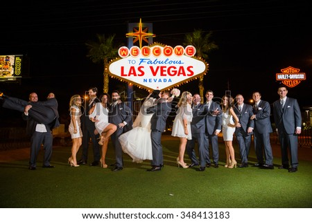 LAS VEGAS, NV - DECEMBER 12, 2014: Wedding party with the bride and groom in front of the Las Vegas sign in Nevada at night. - stock photo