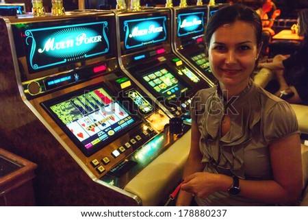 LAS VEGAS, NV- JULY 13, 2013:  Smiling young woman ready to play at slot machine in Bellagio Casino - stock photo