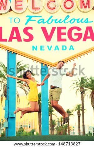 Las Vegas Sign. Happy people jumping having fun in front of Welcome to Fabulous Las Vegas sign. Beautiful young couple on the Strip cheerful and excited during travel holidays vacation, Nevada, USA. - stock photo