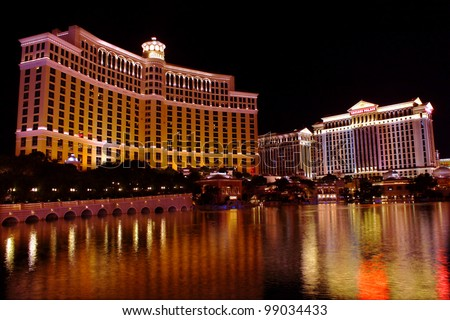 Las Vegas, USA - November 30, 2011:  A large fountain pool is situated in front of the Bellagio Hotel with neighboring Caesars Palace Hotel seen on the right on November 30, 2011 in Las Vegas. - stock photo