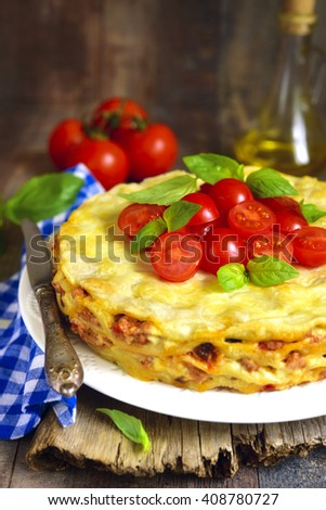 Lasagna pie with chicken and dried mushrooms on a rustic background. - stock photo