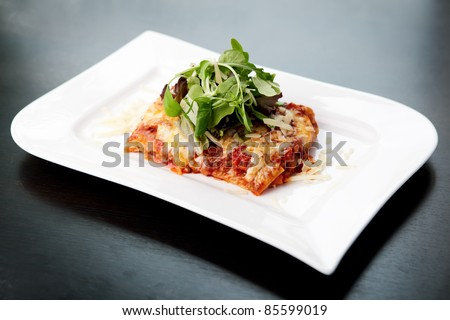 Lasagna served on a white plate with salad - stock photo
