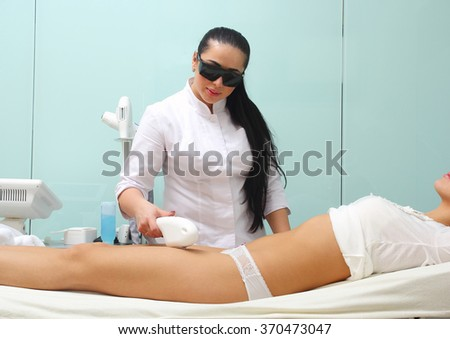 Laser hair removal legs. Beautician makes the procedure body hair removal. - stock photo