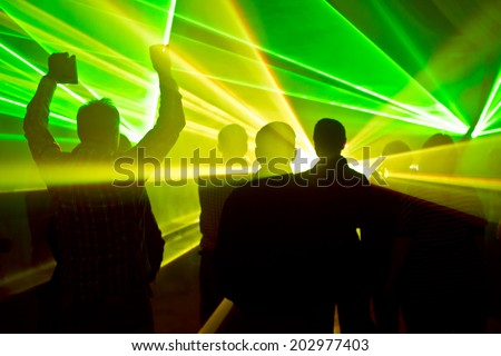 lasers at a nightclub and silhouettes of dancing people - stock photo