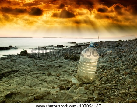 Last bottle of collected fresh water on the coast near the sea. - stock photo