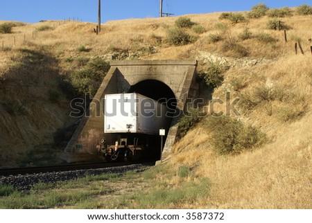 last car of freight train passes through tunnel in Sierra Nevada Range, California - stock photo