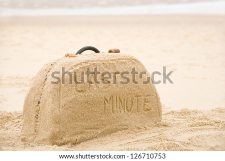 Last minute written on suitcase build out of sand on beach concept - stock photo