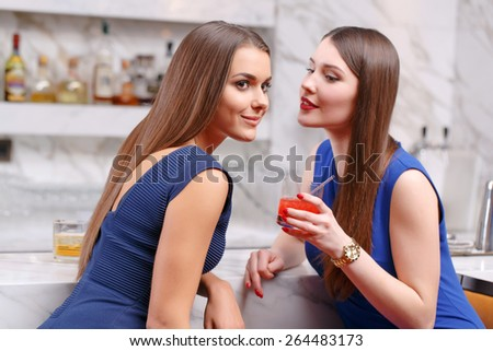 Last news from the friend. Two pretty young girls gossiping while they sit in the bar - stock photo