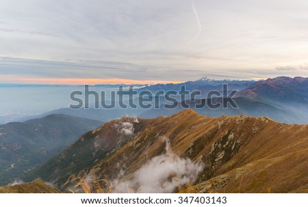 Last red and orange sunlight behind the majestic peaks of M. Viso (3841 m), Italian - French Alps, viewed from distant. Mist in the valley below, autumnal landscape. - stock photo