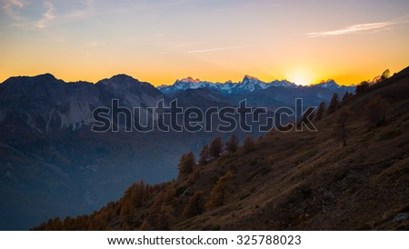 Last red and orange sunlight behind the majestic peaks of the Massif des Ecrins (4101 m), French Alps, viewed from distant in backlight. mist in the valley below, autumnal landscape. - stock photo