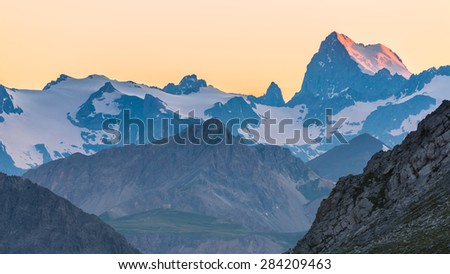 Last red sunlight hitting the glacier on the majestic peak of the Barre des Ecrins (4101 m), France. Telephoto view from distant at high altitude. Clear orange sky. - stock photo