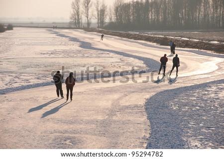 last skaters in back-light going home before sunset - stock photo