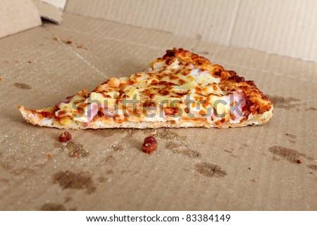 Last slice of pizza left in the box - stock photo