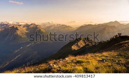 Last soft sunlight over rocky mountain peaks, ridges and valleys of the Alps at sunset. Extreme terrain landscape at high altitude in Valle d'Aosta, scenic travel destination in Italy. - stock photo