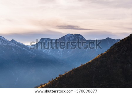 Last sunlight hitting a steep ridge in the foreground with scenic cloudscape and moody sky over majestic snocapped mountain range in the background. Mist in the valley below, Italian French Alps. - stock photo