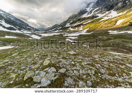 Last warm sunlight on alpine valley with glowing slopes and green meadows. Wide angle view from above with rocky terrain in the foreground. - stock photo