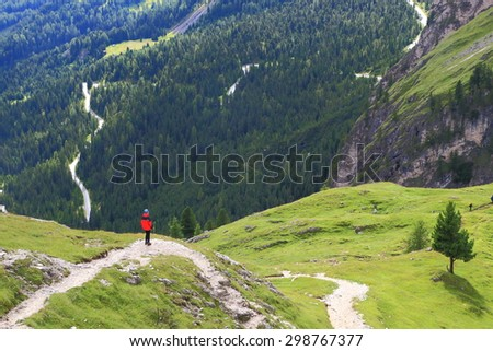 Lasties Valley and distant mountaineer surrounded by green meadows, Sella massif, Dolomite Alps, Italy - stock photo