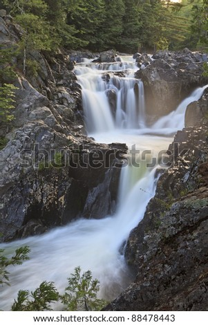 Late afternoon sun on the mist above Split Rock Falls in the Adirondack Mountains of New York - stock photo