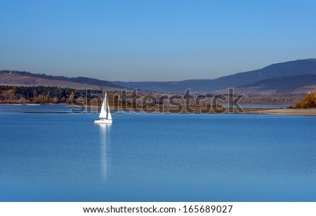 Late autumn view portraying deep waters of Orava reservoir and white yacht in the distance. Orava reservoir is popular destination located near Namestovo town, Slovakia. - stock photo