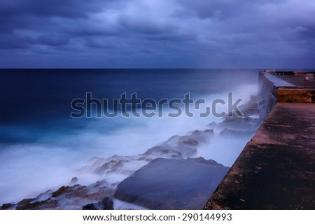 Late evening after the sunset by the walls of the Malecon esplanade in Havana, Cuba and dramatic sea bounding water on the rocks with stormy skies on background. - stock photo