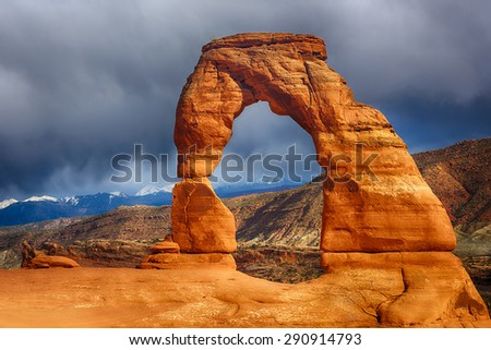Late evening photo of a Delicate Arch with a dramatic stormy sky in the back. Arches National Park, Utah - USA  - stock photo