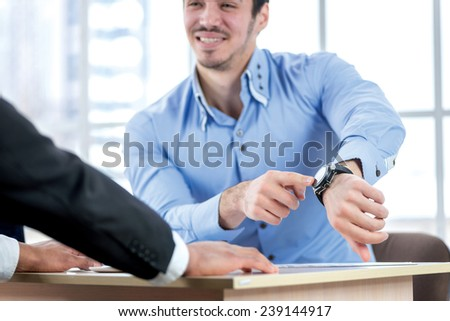 Late for work. Businessman points at his watch while two successful businessman sitting at the table against each in the business office in formal wear and work at a laptop. - stock photo