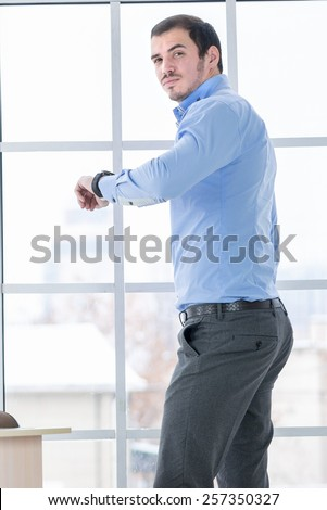 Late for work when time is money. Confident businessman standing in an office and looking at his watch while his desk business notebook on the table - stock photo