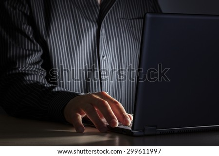Late night internet addiction or working late man using laptop at a desk in the dark - stock photo