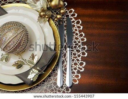 Latest trend of gold metallic theme Christmas  formal dinner table place setting with fine bone china, bauble and festive decorations, with copy space for your text here. - stock photo