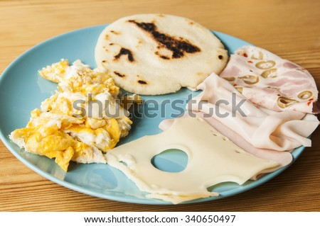 Latin american breakfast: arepa with scrambled eggs, turkey ham and cheese. - stock photo