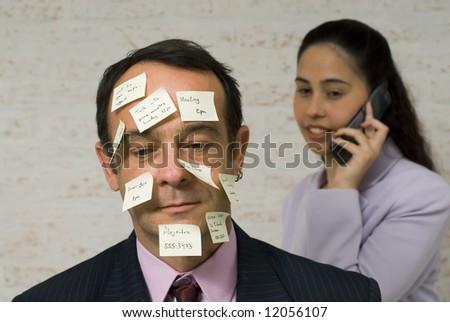 Latin american businessman covered in post-it notes with a woman on the phone in the background - stock photo