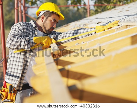latin american construction worker on house roof with measuring tape. Copy space - stock photo