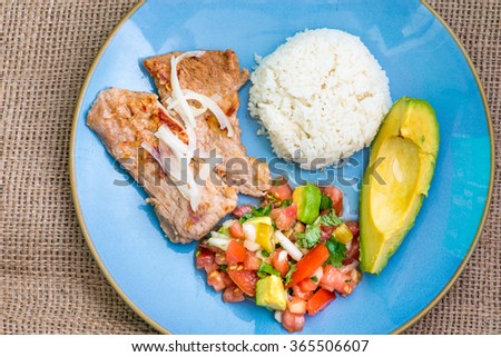 Latin American cuisine fusion: pork steak, white rice,pico de gallo and avocado.Mexican and Cuban cuisine fusion produces a healthy balanced plate of food - stock photo