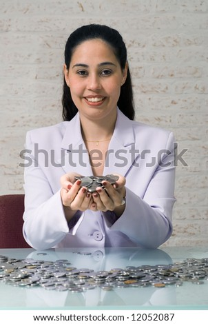 Latin american woman in a business suit pouring money onto an office desk. - stock photo