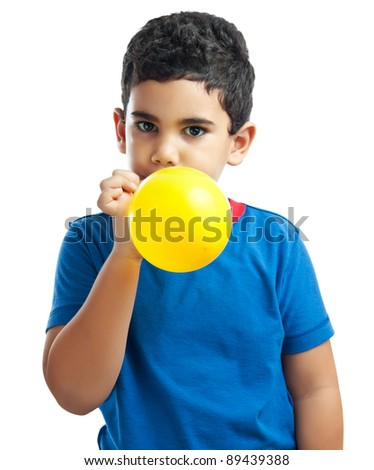 Latin boy blowing a yellow balloon isolated on a white background - stock photo