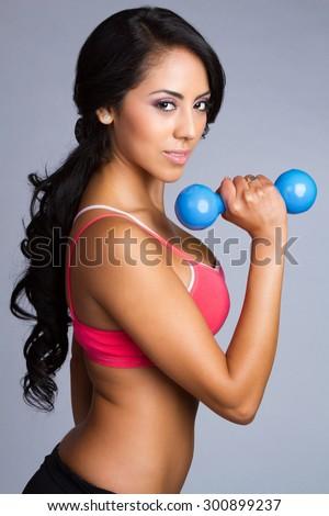 Latin fitness woman lifting weights - stock photo