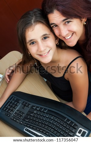 Latin girl and her beautiful mother working on a computer at home ( Image taken from above with the subjects smiling at the camera) - stock photo