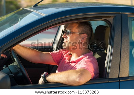 Latin guy trying to be as cool as possible behind the wheel - stock photo