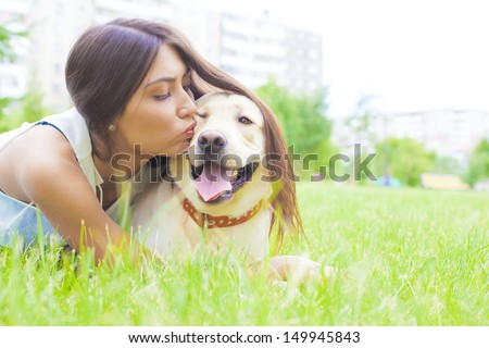 Latin Hispanic brunette young girl kissing her white dog in the city park on the background of the house Copy space for inscription  - stock photo