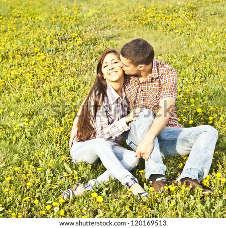 latin hispanic Romantic young couple kissing outdoors in park smiling - stock photo