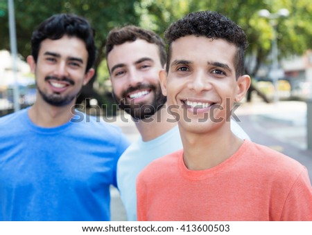 Latin man with two friends in the city with buildings and park in the background - stock photo