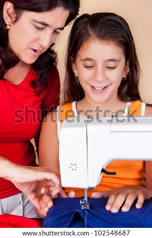 Latin  mother teaching her daughter how to use a sewing machine - stock photo