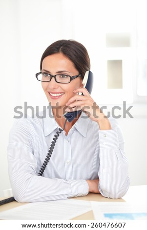 Latin receptionist with spectacles conversing on the phone while smiling at her workplace - stock photo