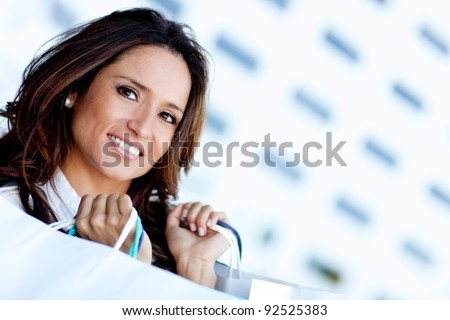 Latin shopping woman holding paperbags and smiling - stock photo
